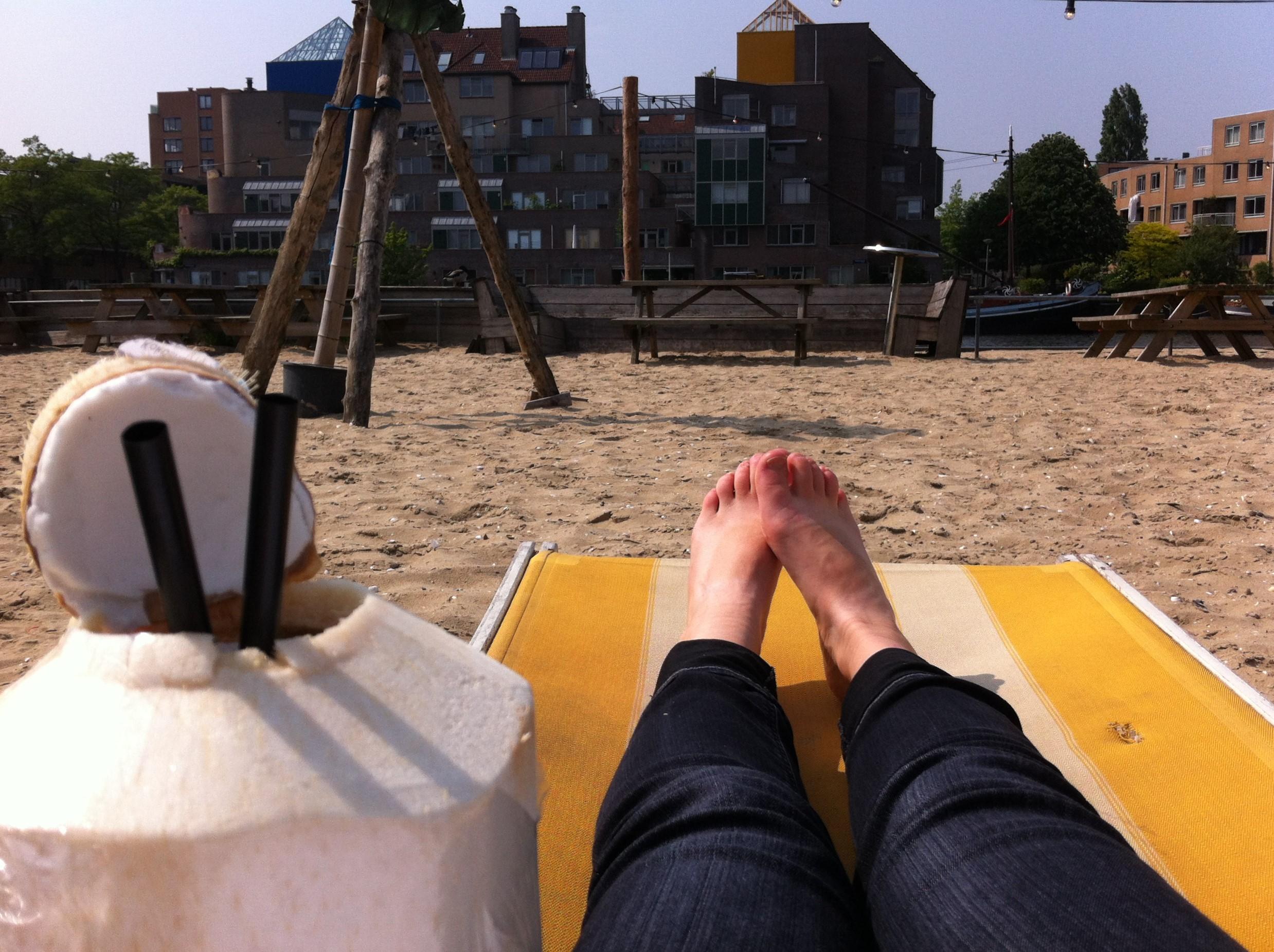 Relaxen met een verse kokosnoot op een strandstoel op dagstrand Roest in Amsterdam
