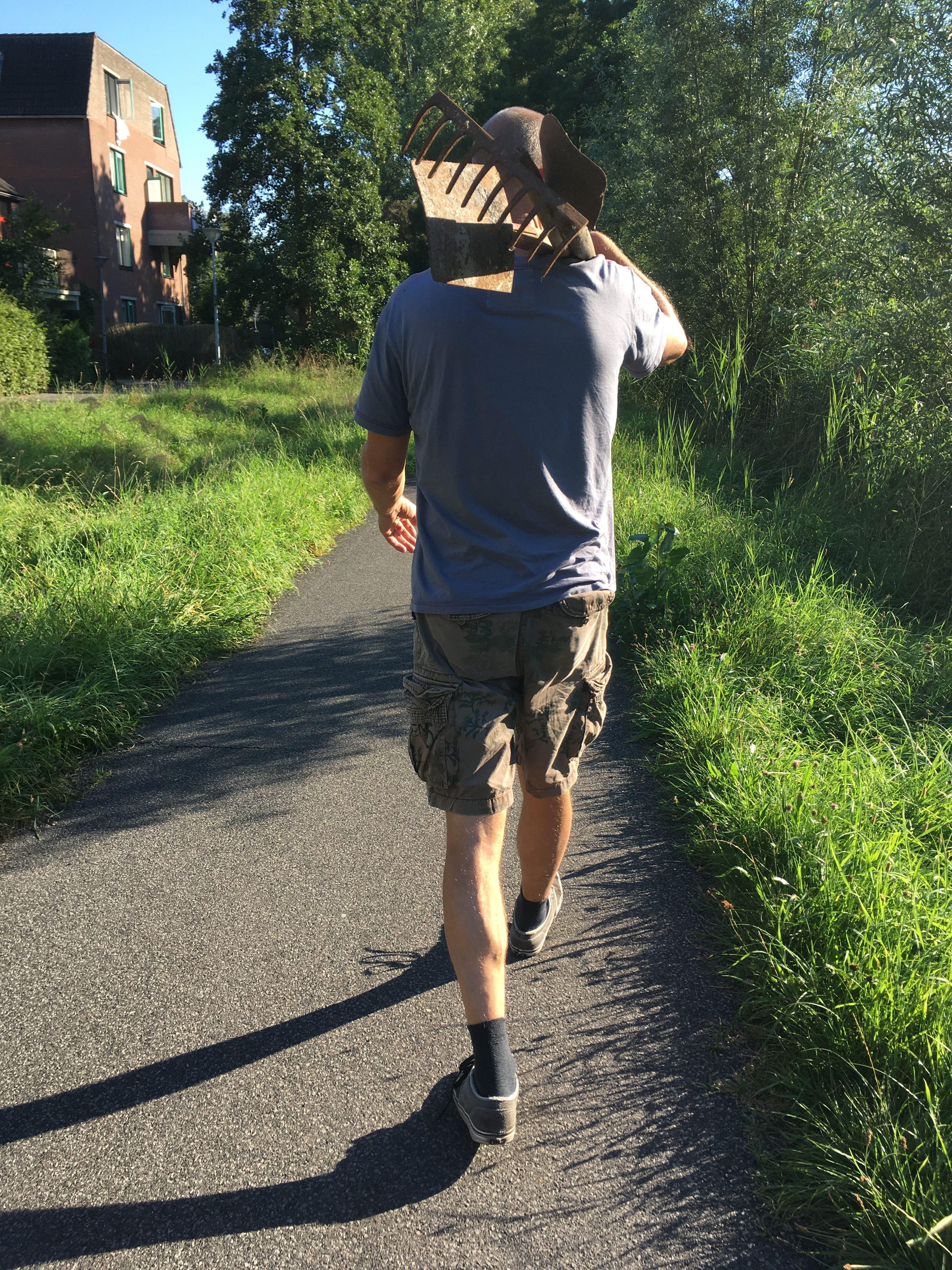 Onderweg naar moestuin met tuingereedschap.