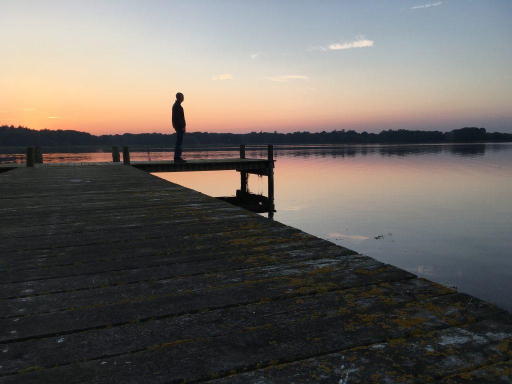 Tom op steigertje tijdens zonsondergang in Nysted baai.